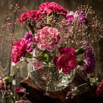 Bouquet di garofano rosa in vaso di vetro sulla vecchia superficie in legno. festa della mamma, biglietto di auguri di compleanno