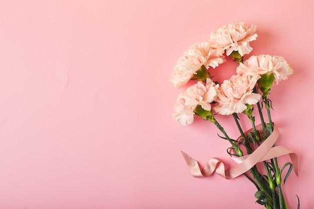 Mazzo di bouquet di garofani rosa su sfondo rosa da tavola