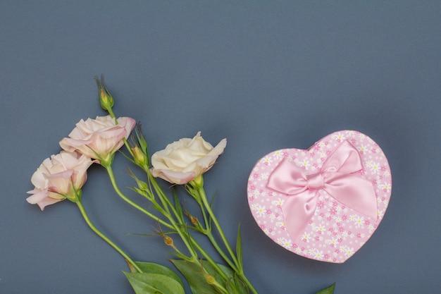 Bouquet di fiori rosa con foglie e confezione regalo a forma di cuore su sfondo grigio. vista dall'alto. concetto di giorno di celebrazione.