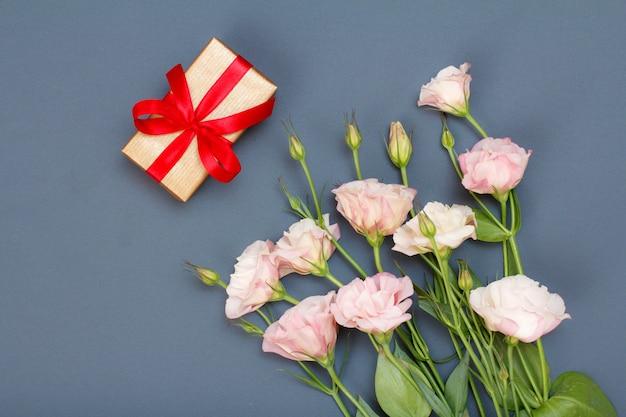 Bouquet di fiori rosa con foglie e confezione regalo con nastro rosso su sfondo grigio. vista dall'alto. concetto di giorno di celebrazione.