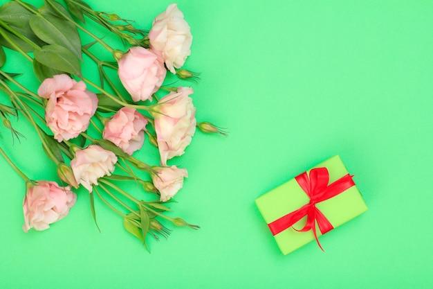 Bouquet di fiori rosa con foglie e confezione regalo con nastri rossi su sfondo verde. vista dall'alto. concetto di giorno di celebrazione.