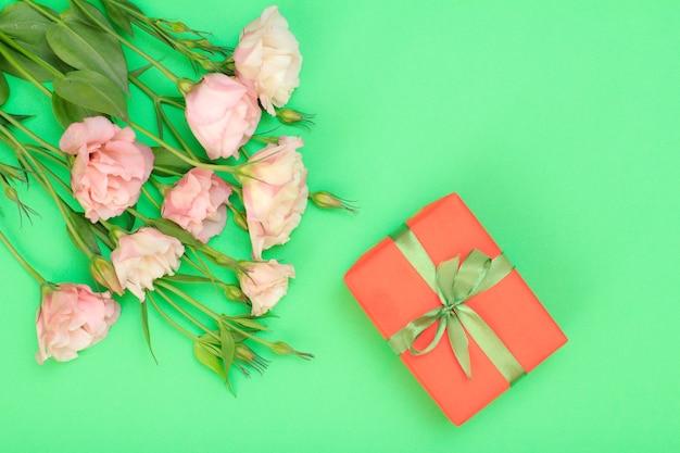 Bouquet di fiori rosa con foglie e confezione regalo con nastro su sfondo verde. vista dall'alto. concetto di giorno di celebrazione.