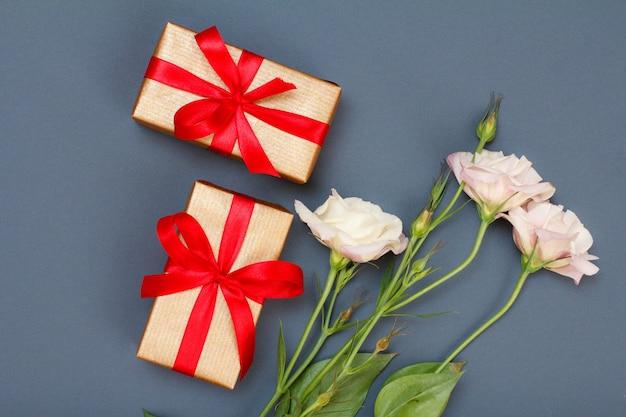 Bouquet di fiori rosa con foglie e scatole regalo con nastri rossi su sfondo grigio. vista dall'alto. concetto di giorno di celebrazione.