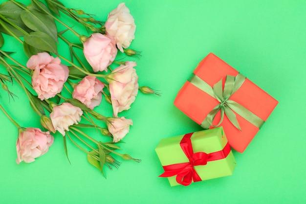 Bouquet di fiori rosa con foglie e scatole regalo con nastro su sfondo verde. vista dall'alto. concetto di giorno di celebrazione.