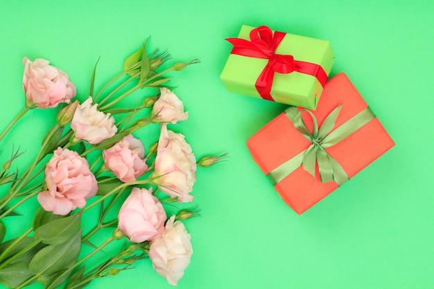 Bouquet di fiori rosa con foglie e scatole regalo con nastri su sfondo verde. vista dall'alto. concetto di giorno di celebrazione.