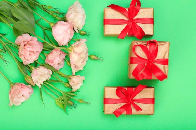 Bouquet di fiori rosa con foglie e tre confezioni regalo su sfondo verde. vista dall'alto. concetto di giorno di celebrazione.
