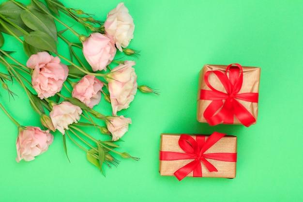 Bouquet di fiori rosa con foglie e due confezioni regalo su sfondo verde. vista dall'alto. concetto di giorno di celebrazione.