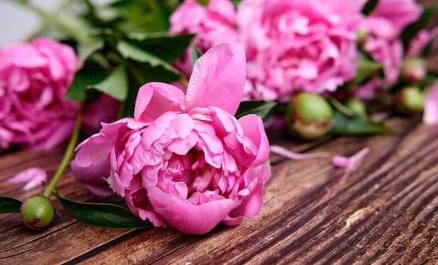 Un bouquet di peonie rosa in linea su una superficie di legno scuro