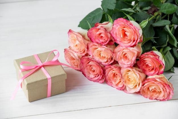 Bouquet di rose rosa e confezione regalo con fiocco rosa su fondo di legno bianco. san valentino, compleanno, festa della donna e altre festività.