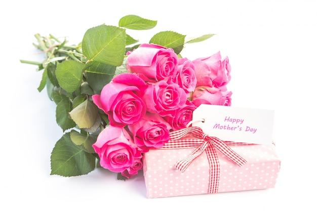Bouquet di rose rosa accanto a un regalo con una carta di buon compleanno