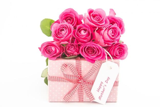 Mazzo delle rose rosa accanto ad un regalo rosa con una carta felice di giorno di madri su fondo bianco