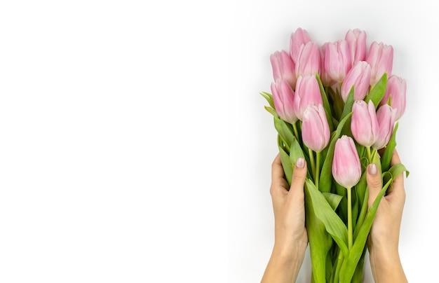 Mazzo di tulipani rosa in mani femminili biglietto di auguri festivo per le vacanze