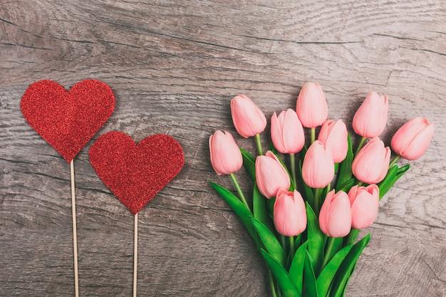 Mazzo dei tulipani rosa e di due cuori rossi da carta, su fondo di legno