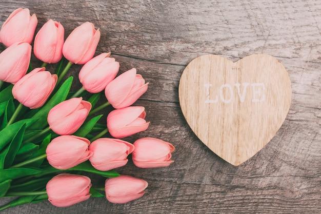 Mazzo di tulipani rosa e un biglietto di s. valentino a forma di cuore da legno, su un fondo di legno