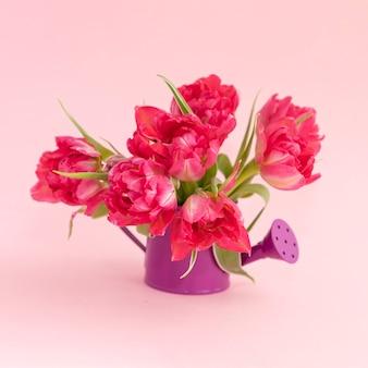 Bouquet di tulipani rosa in un vaso a forma di annaffiatoio.