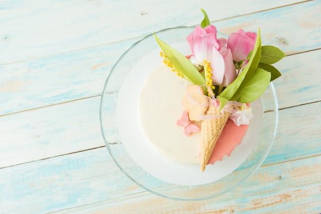 Mazzo dei tulipani rosa su una torta bianca del biscotto