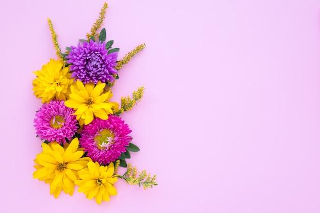 Bouquet di astri viola e margherite gialle su uno sfondo di carta rosa, mockup con spazio di copia