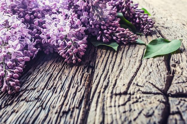Mazzo di lillà viola sulla vecchia tavola di legno.