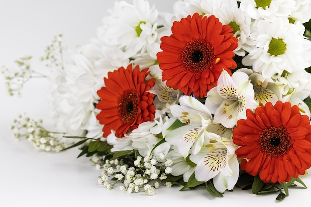 Un bouquet di gerbere rosse, gigli bianchi e margherite, isolato su uno sfondo bianco. regalo.