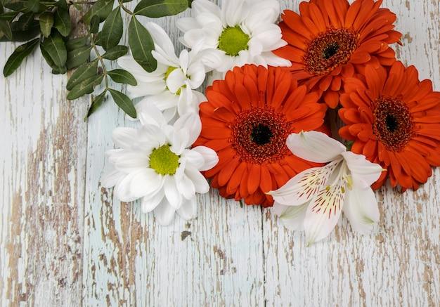 Un bouquet di gerbere rosse, gigli bianchi e margherite, isolato su uno sfondo di legno. regalo