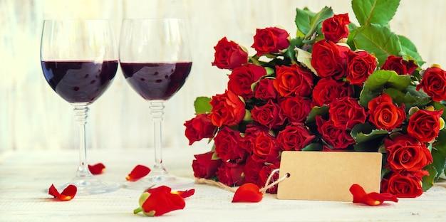 Un bouquet di rose rosse e vino rosso in bicchieri. san valentino. messa a fuoco selettiva. vacanza.