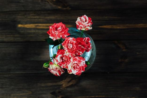 Bouquet di rose rosse in un vaso su uno sfondo marrone da tavole.