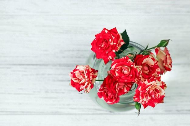 Bouquet di rose rosse in un vaso su sfondo bianco da tavole.