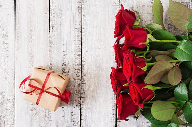 Mazzo delle rose rosse su una tavola di legno.