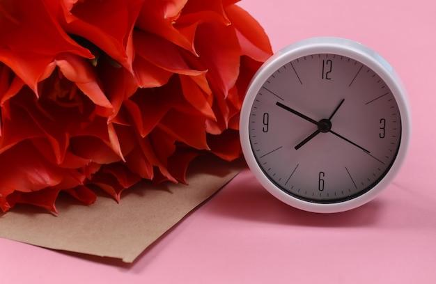 Bouquet di tulipani rossi, orologio su sfondo rosa pastello. festa della mamma o 8 marzo, compleanno.