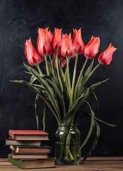 Mazzo di tulipani rossi e pila di libri su sfondo lavagna. scuola ancora in vita
