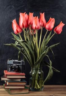Mazzo di tulipani rossi e pila di libri con cinepresa su sfondo lavagna. scuola ancora in vita