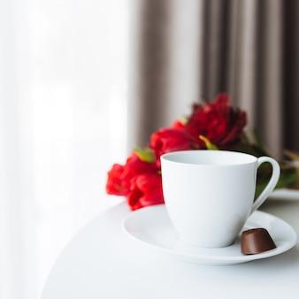Bouquet di tulipani rossi sul tavolo e tazza di caffè bianco