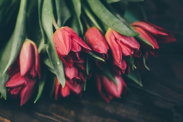 Bouquet di tulipani rossi su un tavolo di legno in uno stile scuro