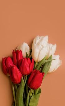 Bouquet di tulipani rossi e bianchi su sfondo marrone. copia spazio