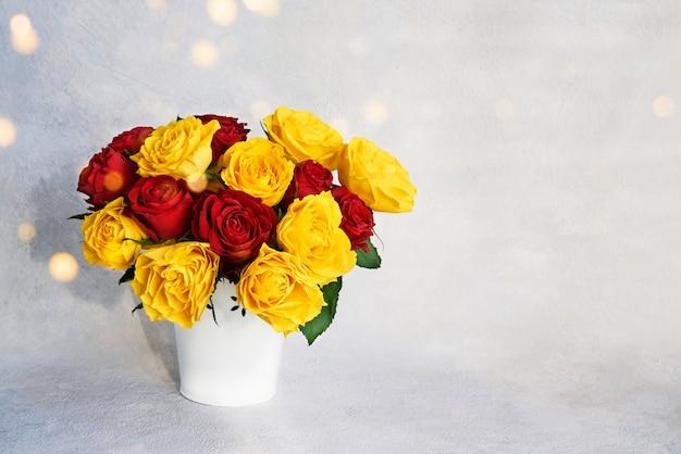 Bouquet di rose rosse e gialle in vaso bianco.