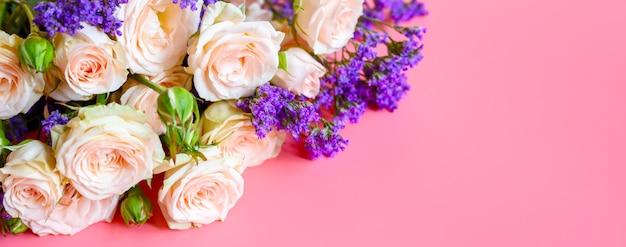 Mazzo di rose e fiori viola luminosi su uno sfondo rosa