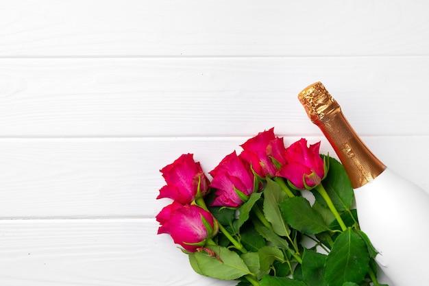 Bouquet di rose e champagne vista dall'alto piatto laici