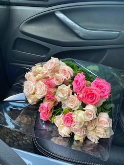 Un mazzo di fiori di rose per la signora sul sedile anteriore dell'auto