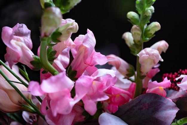 Bouquet di rose e fiori gartens closeup su sfondo nero con profondità di campo ridotta e blu...