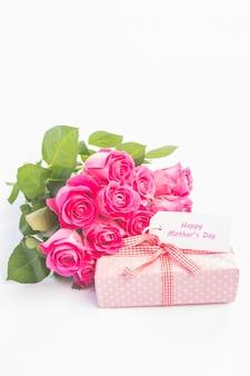 Bouquet di rose accanto a un regalo con una carta del giorno della madre felice