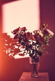 Un mazzo di rose in un vaso di vetro sta su uno sgabello di legno sullo sfondo del muro sotto i raggi del sole.