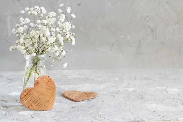 Bouquet di piccoli fiori bianchi e cuori di legno su uno sfondo grigio