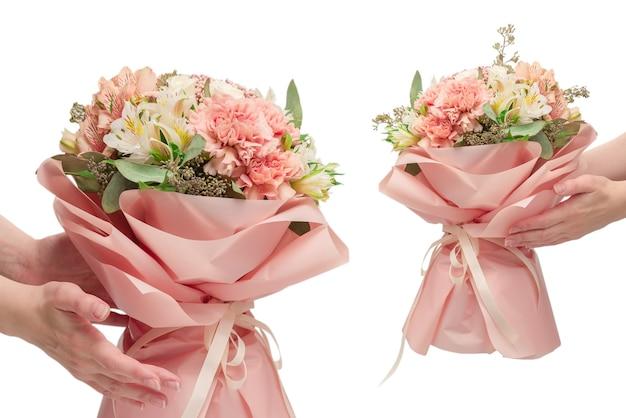 Bouquet di fiori rosa tenui in carta da imballaggio rosa in mani di donna isolate su sfondo bianco.