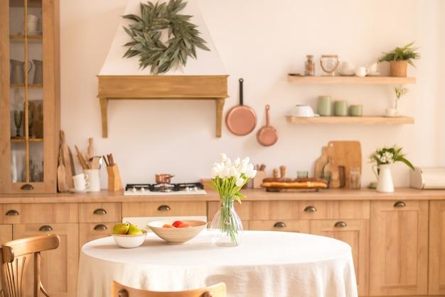 Bouquet di fiori primaverili in un vaso e frutta sul tavolo della cucina