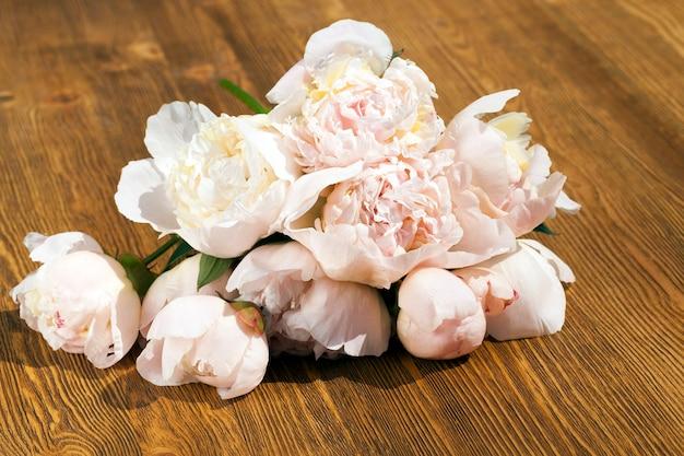 Un bouquet di peonie primaverili, adagiato su una superficie di legno. avvicinamento