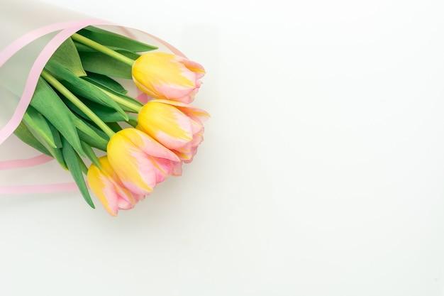 Mazzo di teneri tulipani rosa su sfondo bianco, copia spazio, posto per il testo