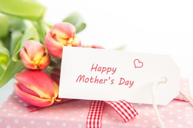 Mazzo di tulipani accanto a un regalo con una carta felice giorno della madre