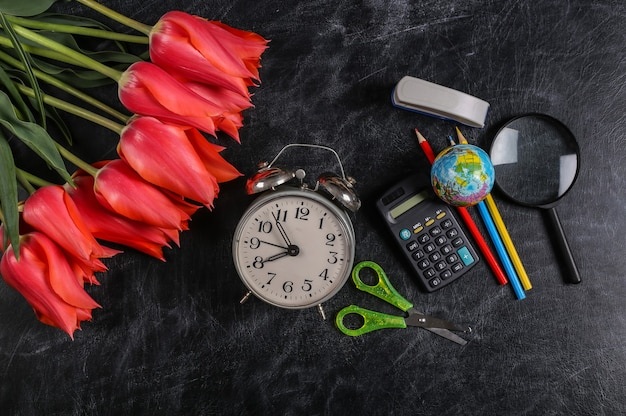 Mazzo di tulipani e materiale scolastico sulla lavagna. conoscenza, festa dell'insegnante, ritorno a scuola. vista dall'alto