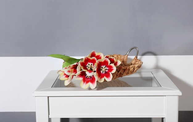 Bouquet di tulipani variegati sul tavolo bianco vicino alla parete a strisce