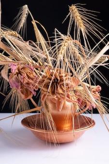 Un mazzo di spighe di grano con fiori secchi in un piatto di rame su un tavolo bianco e uno sfondo nero.